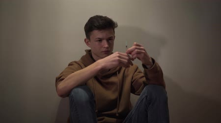 narcomaniac : Camera approaching to teenage Caucasian narcomaniac sitting on the floor with syringe in hands. Addicted boy in casual clothing having drug addiction. Drugs, dependence, harmful habit. Stock Footage