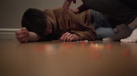 trafficking : Portrait of addicted junkie lying on the floor with pills and syringe scattered around. Unrecognizable man trying to wake narcomaniac up. Overdose, dependence, drug addiction. Stock Footage