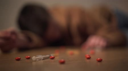 bağımlı : Close-up of pills and syringe lying on wooden floor with blurred boy at the background. Unrecognizable man trying to wake up overdosed Caucasian teenager. Drug addiction, overdose, narcotic. Stok Video