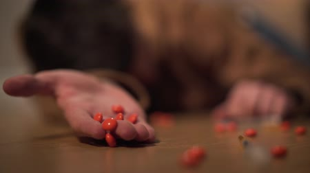 eufória : Close-up of orange drug pills falling out from male Caucasian hand, blurred boy lying on the floor at the background. Young narcomaniac having overdose. Drug dependence, risk, harm.