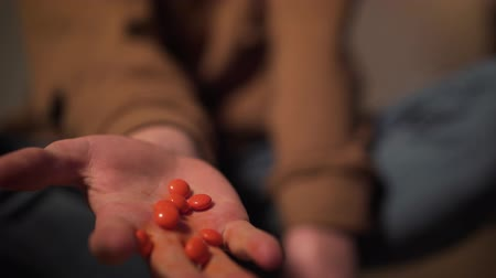 bağımlı : Close-up of male teenage Caucasian hand with orange pills. Unrecognizable addicted boy dropping drugs. Harmful habit, drug addiction, adolescence. Stok Video