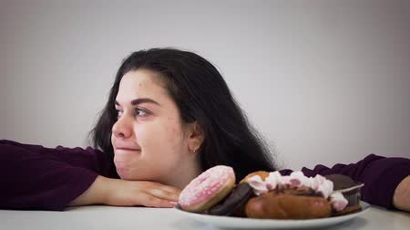 greedily : Portrait of obese Caucasian brunette girl taking dessert from plate and chewing. Funny fat woman eating sweets and looking around. Self control, obesity, lifestyle. Stock Footage