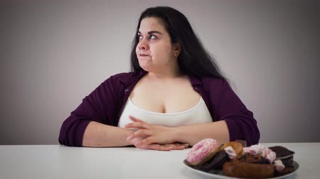 упитанность : Confident Caucasian plump woman looking at plate with dessert and moving it aside. Fat girl controlling herself. Overweight, obesity, healthy lifestyle.