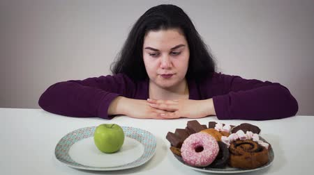 süssigkeiten : Portrait of thoughtful brunette Caucasian woman looking at plates with apple and sweets. Obese girl selecting between healthy and tasty foods. Overweight problem, obesity, eating.