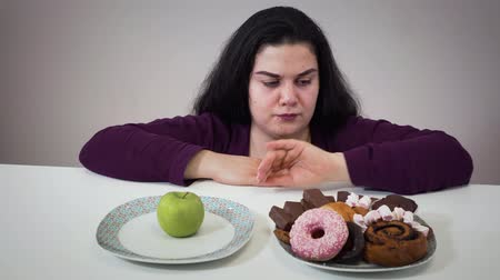 круглолицый : Upset fat Caucasian woman moving aside plate with dessert and taking healthy apple to eat. Sad plump girl dieting. Portrait of woman with overweight problem.