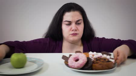 упитанность : Fat Caucasian woman moving aside plate with apple and taking unhealthy sweets to eat. Portrait of smiling plump girl with overweight problem. Obesity, unhealthy lifestyle.