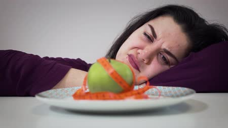 calorias : Close-up of sad Caucasian plump girl looking with disgust at apple. Obese young woman dieting. Portrait of fat girl in front of plate with healthy food and measure tape.