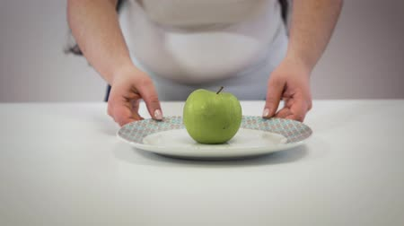 calorias : Female Caucasian hands taking plate with apple and showing folds on belly. Fat young woman having overweight problems. Obesity, fatness, lifestyle.