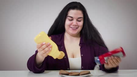 mayonez : Funny brunette Caucasian woman pouring ketchup and mayonnaise on bread and smiling. Plump cheerful girl pouring dressing into mouth and looking at camera. Unhealthy eating, obesity, overweight.