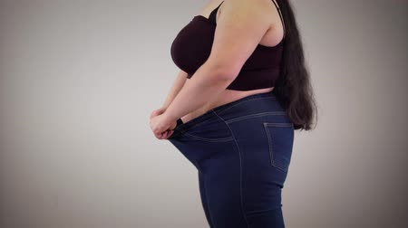 dobras : Side view of plump Caucasian woman showing stretchable jeans. Fat young unrecognizable girl getting dressed indoors. Overweight, obesity, cellulite. Stock Footage