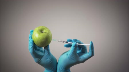 farmacologia : Female hands in medical gloves making injection in apple. Healthy and unhealthy eating, GMO products, chemistry. Stock Footage