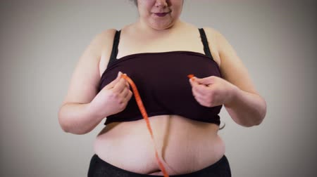 dobras : Cheerful fat Caucasian girl measuring chest with tape meter. Obese woman in underwear having overweight problem. Unhealthy lifestyle, obesity.