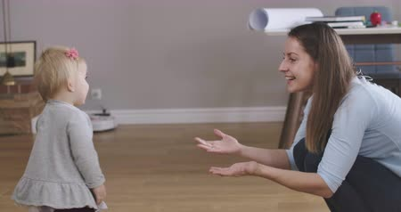 kino : Side view of happy smiling mother asking her baby daughter to come up. Cute little Caucasian girl doing first steps. Childhood, happiness, joy of motherhood. Cinema 4k ProRes HQ.