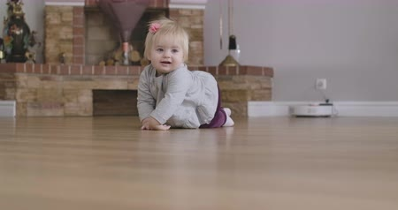ползком : Portrait of joyful Caucasian baby girl with blond hair and grey eyes crawling on the floor. Cheerful child having fun at home. Leisure, resting, childhood, lifestyle. Cinema 4k ProRes HQ.