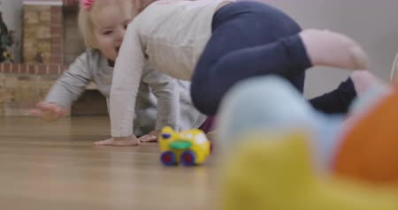 ползком : Cute Caucasian baby girl and her little sister crawling on the floor at home. Happy sisters having fun indoors. Leisure, resting, childhood, lifestyle. Cinema 4k ProRes HQ. Стоковые видеозаписи
