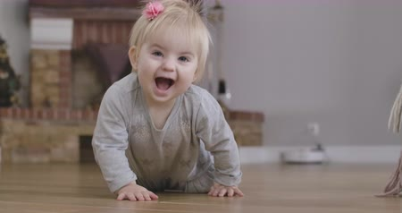 ползком : Cheerful blond Caucasian baby girl with grey eyes crawling to camera on the floor. Cute child having fun at home. Leisure, resting, childhood, lifestyle. Cinema 4k ProRes HQ.