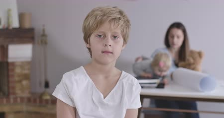 kino : Portrait of blond Caucasian boy with grey eyes looking at camera as his sister and mother playing with teddy bear at the background. Child in white T-shirt posing at home. Cinema 4k ProRes HQ.