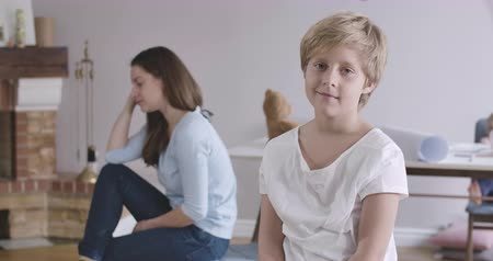 omini : Portrait of handsome Caucasian boy with grey eyes and blond hair looking at camera. His brunette mother and little sister sitting at the background. Child in posing at home. Cinema 4k ProRes HQ. Filmati Stock