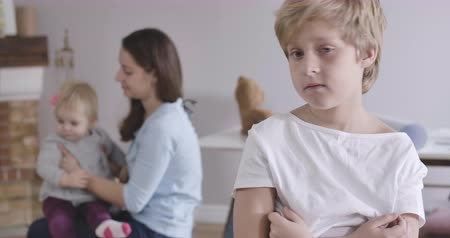 kino : Portrait of upset Caucasian boy with grey eyes looking back at his sister and mother playing, turning back and looking away. Guy in white T-shirt posing at home. Cinema 4k ProRes HQ. Dostupné videozáznamy