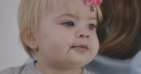 kino : Side view of pretty Caucasian baby girl chewing cookie. Portrait of beautiful child with grey eyes and blond hair. Cinema 4k ProRes HQ. Dostupné videozáznamy