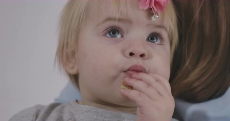 kino : Close-up portrait of cute Caucasian baby girl biting cookie and looking up. Charming child with grey eyes and blond hair. Cinema 4k ProRes HQ.