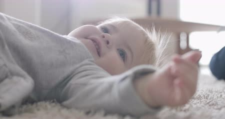 kino : Cute cheerful baby girl lying on soft carpet at home and smiling. Portrait of pretty Caucasian child in sunlight. Cinema 4k ProRes HQ.
