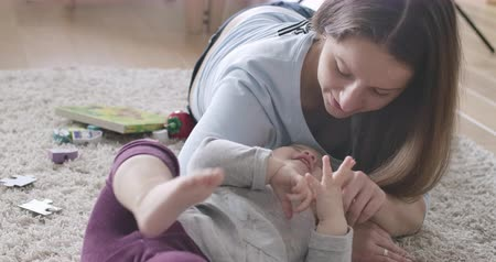 kino : Close-up of young Caucasian mother lying on soft carpet with little girl and touching her fingers. Brunette woman playing with daughter. Happiness, leisure, joy of motherhood. Cinema 4k ProRes HQ.