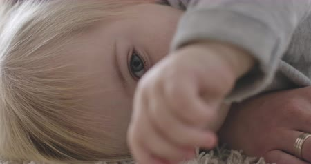 resting : Close-up portrait of extremely beautiful Caucasian baby girl lying on bed. Portrait of calm charming child resting. Cinema 4k ProRes HQ. Stock Footage