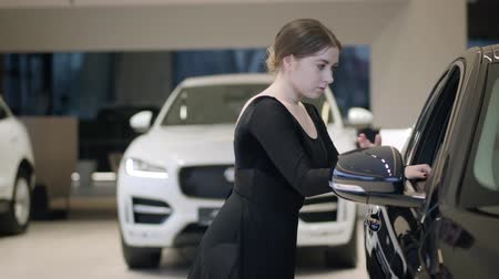 ileri : Charming Caucasian ballet dancer bending back next to black car. Pretty young woman dancing ballet in car dealership. Slim ballerina in auto showroom. Art, automobile industry, classic dance.