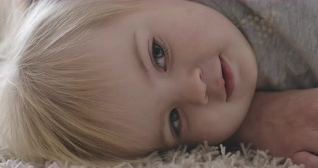 kino : Close-up face of charming Caucasian baby girl with grey eyes and blond hair lying on mothers hand. Portrait of pretty little child resting. Cinema 4k ProRes HQ.