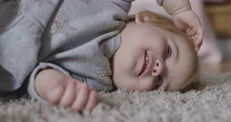 kino : Portrait of cute Caucasian baby girl lying on soft carpet, touching her head, and smiling. Calm charming child resting. Cinema 4k ProRes HQ.