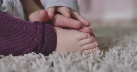 щит : Close-up of female Caucasian hands caressing little babys feet. Tenderness, joy of motherhood, happiness, lifestyle. Cinema 4k ProRes HQ.