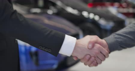 kino : Close-up of male Caucasian hand giving car keys to customer and shaking his hand. Dealer and client making agreement on auto purchase. Car dealership, automobile industry. Cinema 4k ProRes HQ.