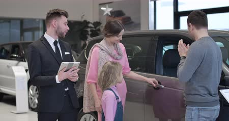 sprzedawca : Young Caucasian family selecting new automobile in car showroom. Man, woman and little cute girl standing with car dealer in auto showroom and talking. Lifestyle, business. Cinema 4k ProRes HQ. Wideo