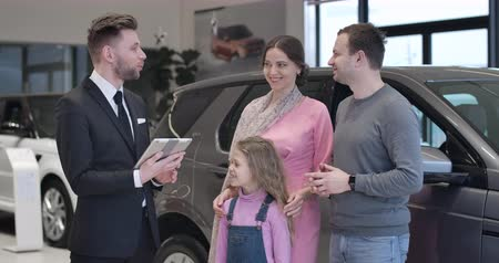трейдер : Confident Caucasian car dealer presenting new automobile to young family. Trader with tablet talking to couple with pretty daughter. Automobile industry, dealership, business. Cinema 4k ProRes HQ.