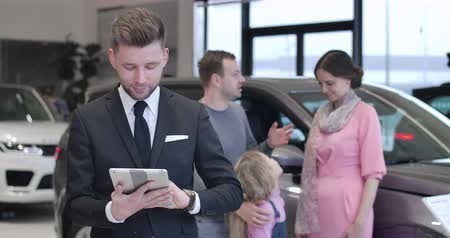 kino : Handsome Caucasian man in suit turning to camera from family discussing car purchase, looking at tablet and signing. Portrait of polite dealer in car dealership. Auto industry. Cinema 4k ProRes HQ.