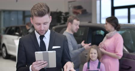 kiállítási terem : Portrait of young confident male car dealer holding tablet and car keys, looking at camera. Young Caucasian family talking at background. Professional trader selling automobile. Cinema 4k ProRes HQ.