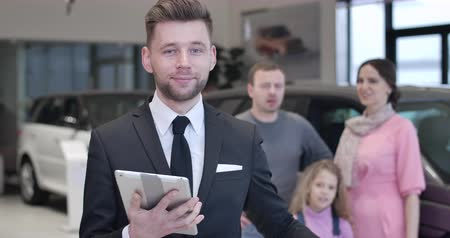 kino : Smiling Caucasian young man looking back at family talking at the background and showing car keys to camera. Positive male dealer selling automobile to customers. Auto industry. Cinema 4k ProRes HQ. Dostupné videozáznamy