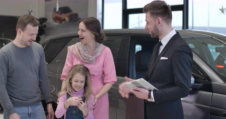 kino : Cute Caucasian little girl taking car keys from dealer, father raising her up. Four people looking at camera and smiling. Happy clients and trader posing in car dealership. Cinema 4k ProRes HQ. Dostupné videozáznamy