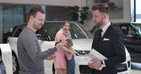 kino : Young Caucasian businessman talking car keys and shaking traders hand as his happy wife and daughter hugging at the background. Successful man buying new car in dealership. Cinema 4k ProRes HQ. Dostupné videozáznamy