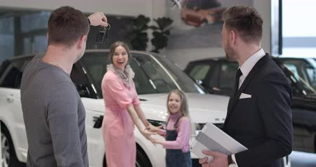 sprzedawca : Happy Caucasian little girl running from background to father buying new automobile and taking car keys. Successful businessman purchasing car for his family. Auto industry. Cinema 4k ProRes HQ. Wideo