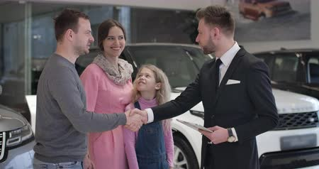 kino : Successful Caucasian businessman shaking car dealers hand and kissing wife on cheek. Cheerful family with pretty little daughter purchasing new vehicle in car dealership. Cinema 4k ProRes HQ. Dostupné videozáznamy