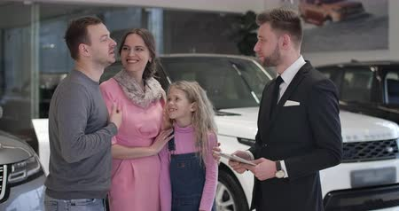 kino : Adult Caucasian man talking with trader in car dealership and touching daughters chin. Young family choosing vehicle in auto showroom. Automobile industry, car showroom, buying. Cinema 4k ProRes HQ.