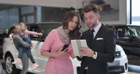 kino : Confident beautiful Caucasian businesswoman talking with car dealer as her husband and daughter standing at the background. Elegant lady buying new automobile in car dealership. Cinema 4k Prores HQ.