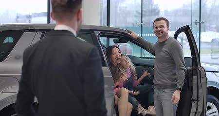 kciuk : Back view of Caucasian male trader standing in car dealership and looking at happy young family in new automobile talking and showing thumbs up. Dealer selling car in showroom. Cinema 4k ProRes HQ.