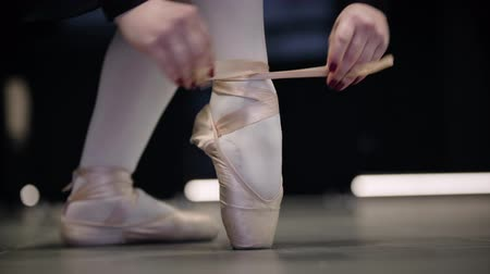 balerína : Close-up feet of Caucasian female ballet dancer tying pointe shoes. Graceful womans hands tying up laces on pointes. Elegance, classic dancing, lifestyle.