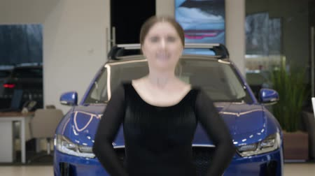 balerína : Smiling Caucasian ballet dancer balancing on tiptoes. Elegant young brunette woman dancing in car dealership in front of vehicle. Camera moving down from dancers face to feet. Elegance, automobiles.