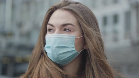 antibody : Portrait of young brunette woman standing on street and looking around. Close-up of beautiful womans face in protective mask. Coronavirus, hazard, danger, global problem.
