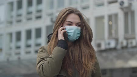 infectious : Young beautiful woman in protective mask standing in city and talking on the phone. Ill brunette girl coughing. Global hazard, transmissible virus, epidemic.