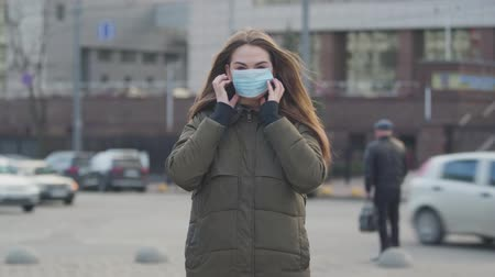 mortality : Middle shot of young brunette woman standing on city street and putting on protective mask. Anxious woman protecting herself against epidemic virus. Pandemic, infection, global catastrophic.